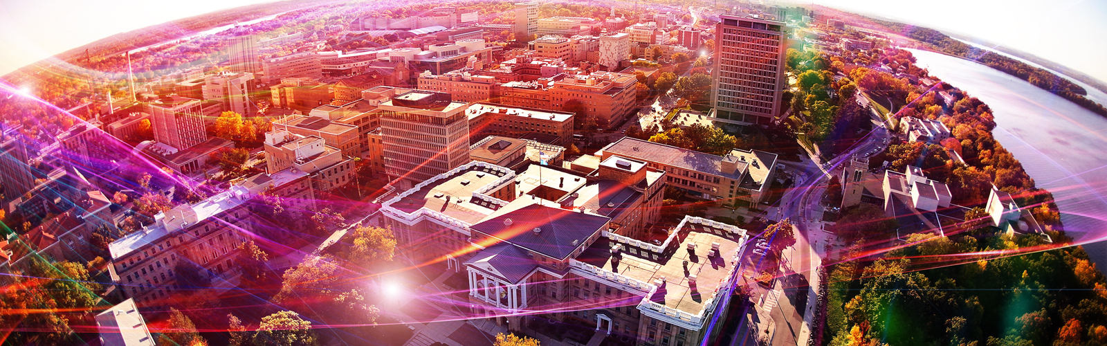Aerial photo of UW–Madison above Bascom Hill with various colored light streaks representing network data and speed.