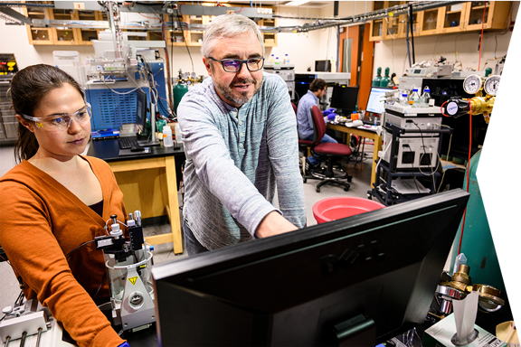 Michael Westphall, distinguished instrument innovator in the Biotechnology Center, consults with postdoctoral fellow Jean Lodge about modifications for a mass-spectrometry, research test she is conducting.