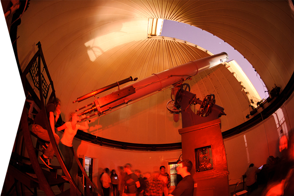 With moonlight shining in an open slit of the Washburn Observatory dome at the University of Wisconsin-Madison, the general public takes advantage of a once-monthly opportunity for nighttime public viewing of the stars using the observatory's vintage telescope.